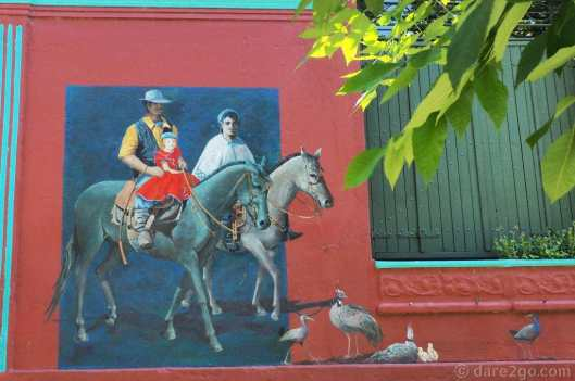 Dark red coloured house with murals depicting traditional gaucho scenes in 25 de Agosto - Gaucho family and native birds outside the frame
