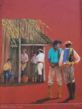 Dark red coloured house with murals depicting traditional gaucho scenes in 25 de Agosto - Gauchos standing around