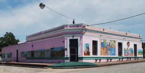 Pink corner building in 25 de Agosto with a collection of murals