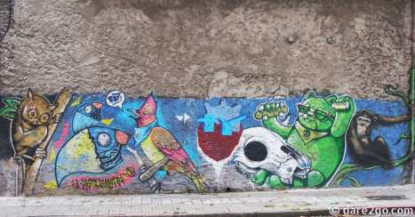 Calle Yaguaron, Montevideo: a long wall section covered in street art - mostly showing wild animals.