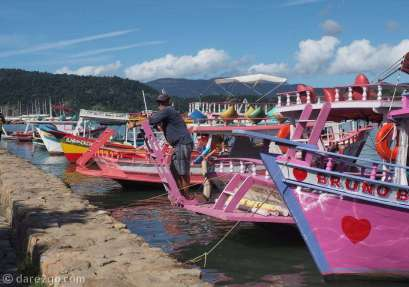 Quiet off-season: a boat owner waiting for tourists to take out into the waters around Paraty. There are hundreds of colourful boats catering for tourists.