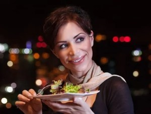 Pretty woman having dinner at night in outdoors restaurant, eating fresh green salad, healthy nutrition, with pleasure spending evening on the party
