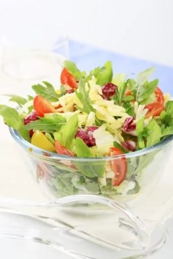 Bowl of spring salad sprinkled with grated cheese