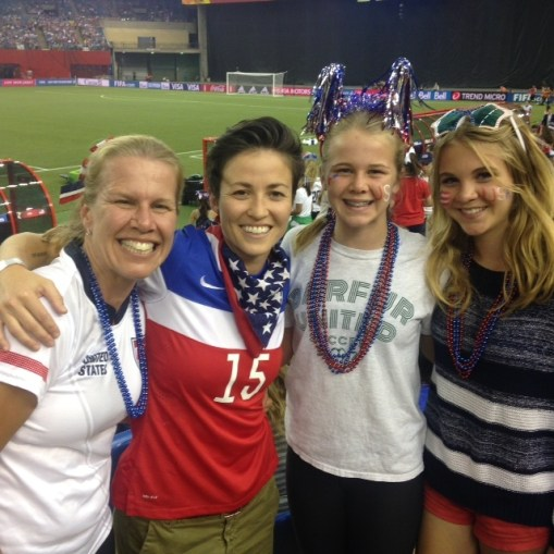 """Dr."" Alex Nuttall-Smith and Rachael Rapinoe, both recipients of the DU Spirit Award, at the Women's World Cup in June 2015 with Ella and Julia Nuttall-Smith."