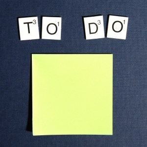 A yellow sticky note with the words 'to do' spelled out in Scrabble(TM) tiles