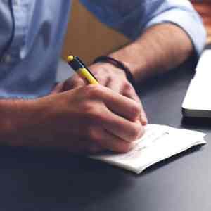 A person wearing a black shirt writing in a notebook with a blue pen
