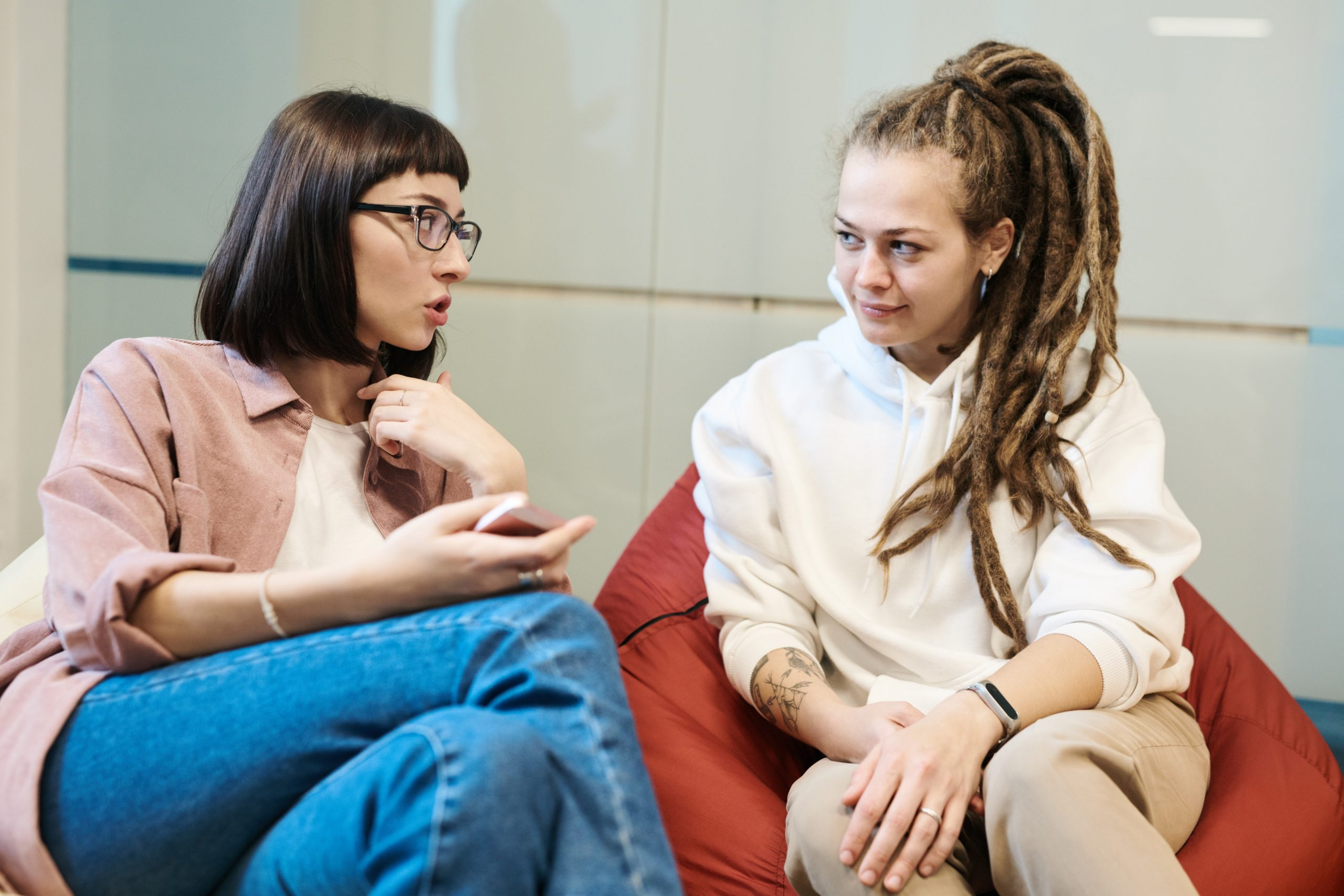Photo of two women talking while sitting on beanbags