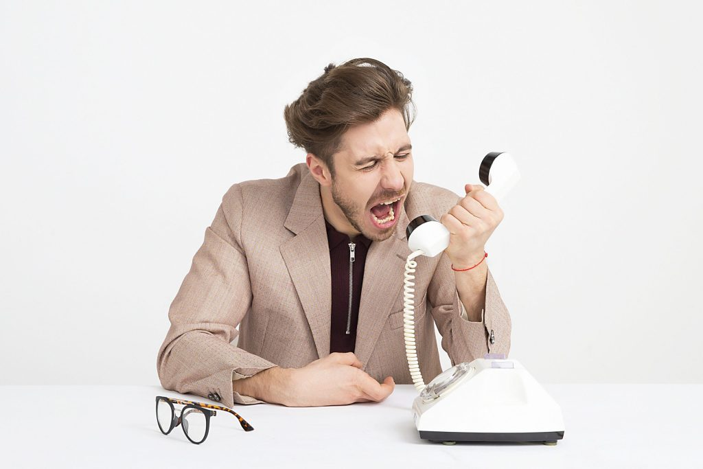 A man yelling into an old-style white telephone, with glasses sitting on the table in front of him