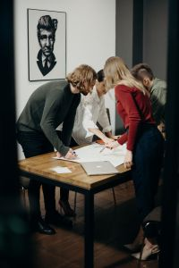 People standing around a table covered in paperwork