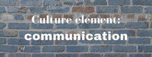 "A blue-painted brick wall with the words ""Culture element: communication"" superimposed in white"