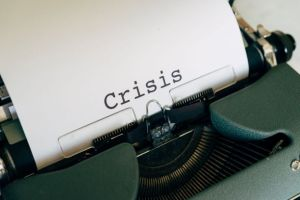 "A typewriter with the word ""crisis"" in the centre of a white sheet of paper"