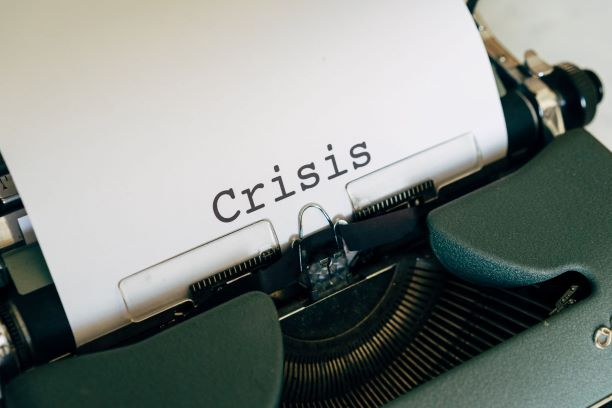 """A typewriter with the word """"crisis"""" in the centre of a white sheet of paper"""