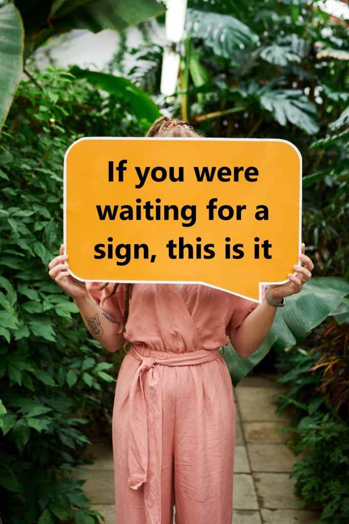 "A woman holding a sign saying ""If you were waiting for a sign, this is it"""