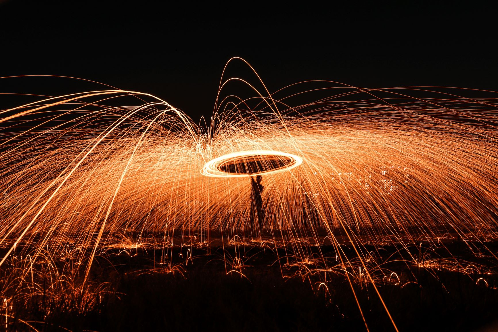 A long exposure photograph of a person swinging a large sparkler over their head