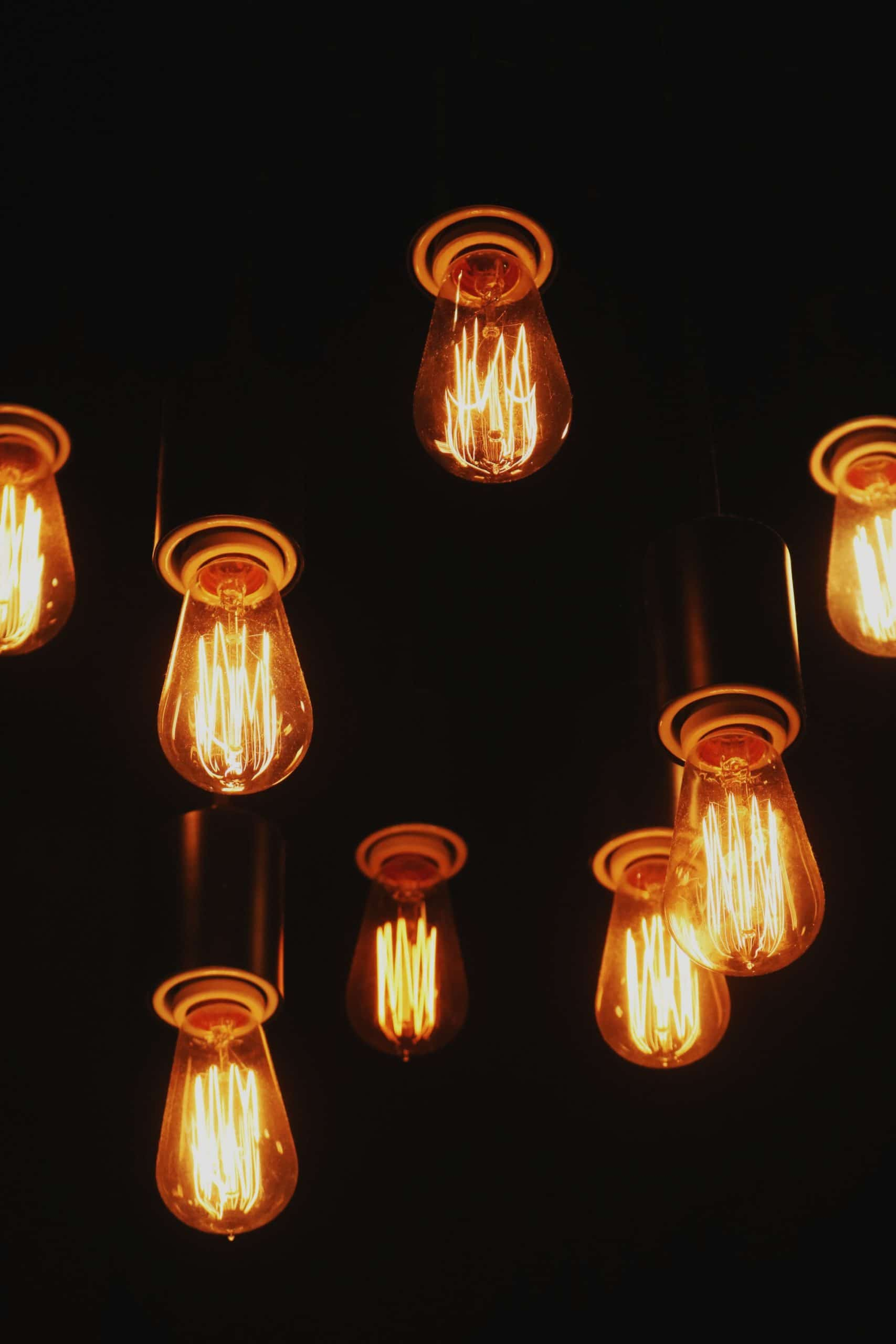 A photo of unshaded lightbulbs handing from a ceiling
