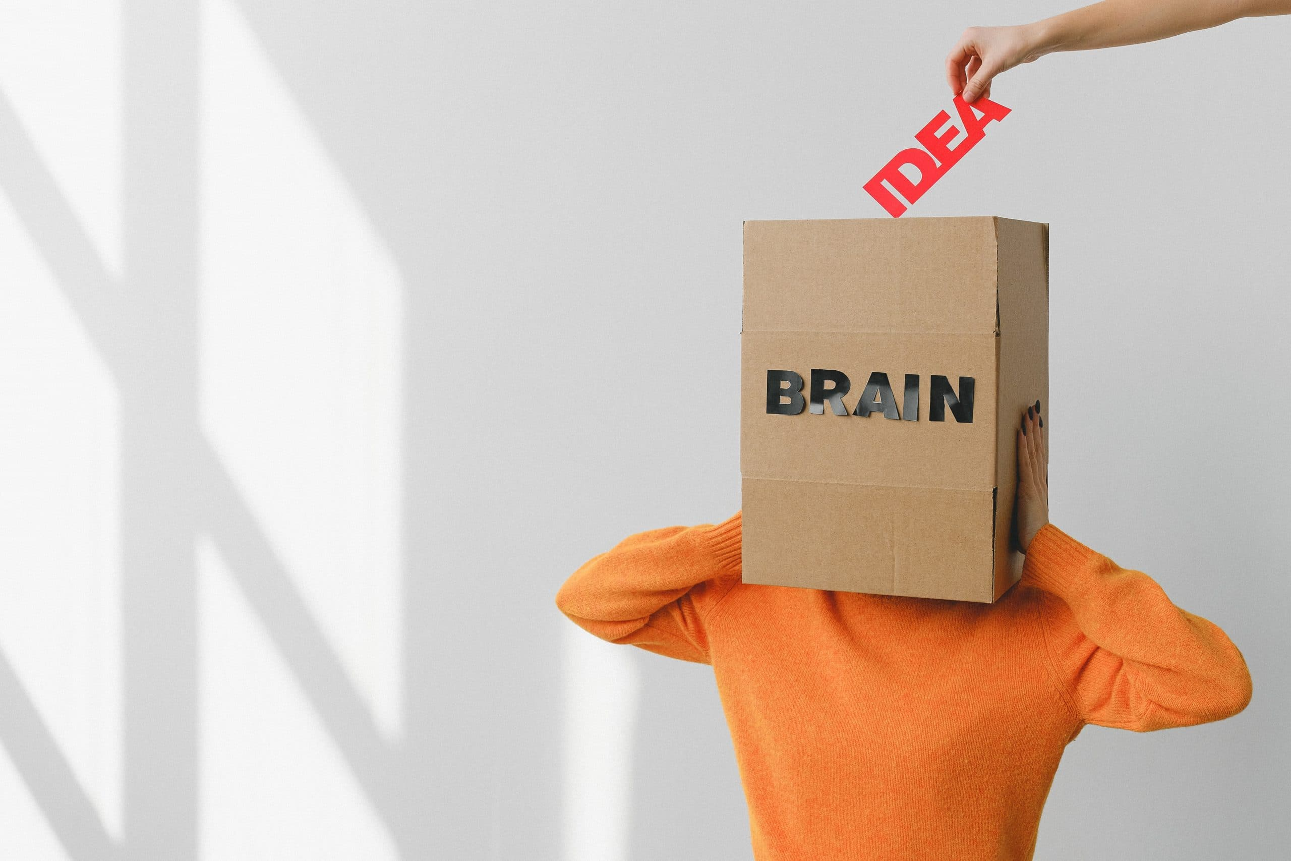 """A photo of a person with a box over their head labelled """"brain"""" and a hand putting the word """"idea"""" into the box"""