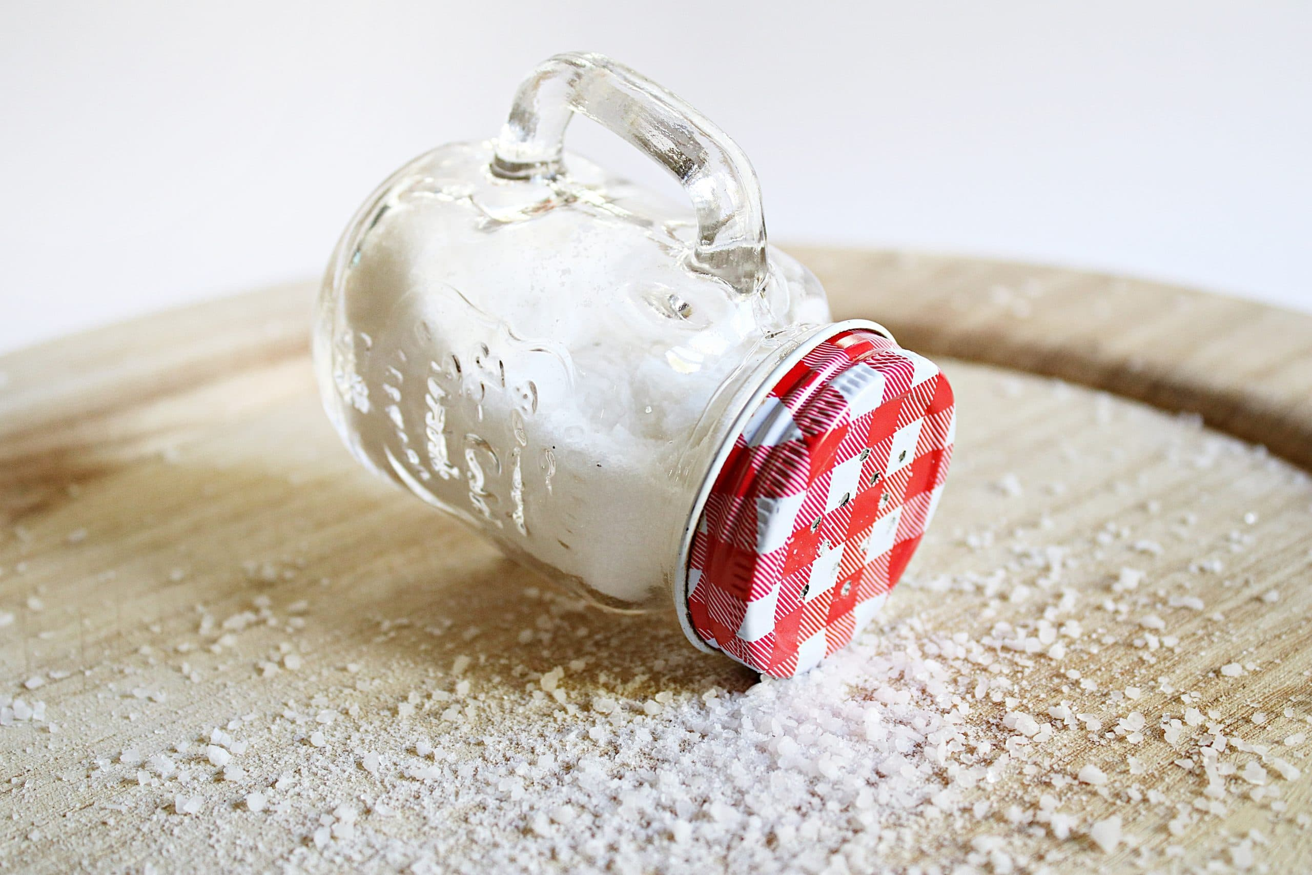 A glass container of salt with a red lid, lying on its side on a wooden board, with salt crystals sprinkled around