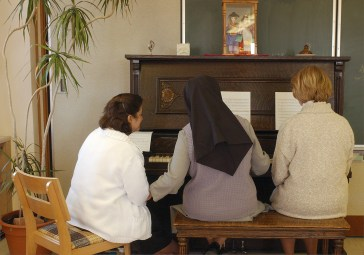 """Sister Cecilia Polt, center, teaches piano lessons to postulants Chris Velila, left, and Ann Dana, right, at the monastery. SUMMARY: """"LIFE INSIDE THE IMMACULATA MONASTERY"""" """"So faith, hope, love remain, these three: but the greatest of these is love."""" -- 1st Corinthians 13:13. The 40 Benedictine sisters of the Immaculata Monastery in Norfolk live by that Bible verse. They start and end each day with prayer. These images are just a small glimpse into their lives."""