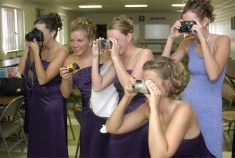 Bridal party members photograph the bride before a wedding at Christ Lutheran Church in Norfolk on Saturday, July 12, 2003.