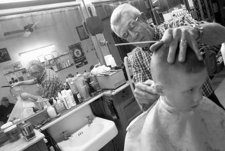 Lavern Scott, owner of Scotty's Barber Shop in Randolph, cuts 6-year-old Nolan Nordhues hair Tuesday afternoon, March 19, 2002. Scott has owned the barber shop since May of 1962.