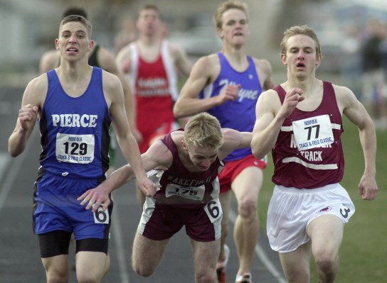 Aaron Lueth of Wakefield (center) stumbles between Aaron Blank of Pierce (left) and Josh Dodson of Norfolk (right) as they near the finish line of the boys 800 meter run Thursday, April 25, 2002.