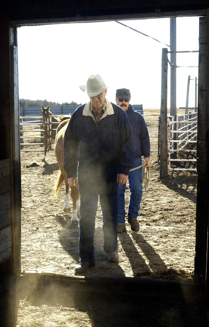 Retired Nebraska Senator 'Cap' Dierks walks into his barn on his ranch south of Ewing Friday, Dec. 13, 2002, followed by his ranch hand Les Green and horse Gabe. Dierks is spending more time on his ranch since retiring.