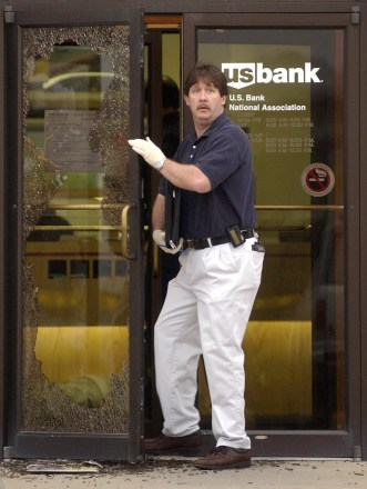 Norfolk police investigator Randy Raney comes out of a shattered glass door at the US Bank branch office while investigating an armed robbery that ended with 5 people shot to death Thursday morning, Sept. 26, 2002.