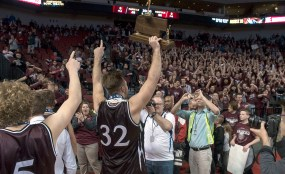 DARIN EPPERLY/DAILY NEWS LINCOLN -- Logan Strom of Norfolk hoists the Class A championship trophy for the student section to see as they leave the arena floor on Saturday night at Pinnacle Bank Arena. 3-11-17