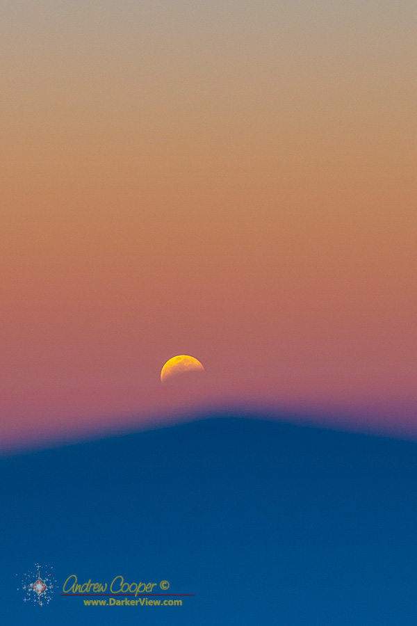 The shadow of Mauna Kea below a moon sliding into the Earth's shadow during a sunset lunar eclipse