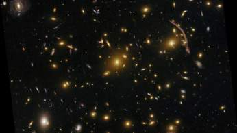 NASA's Hubble Space has peered nearly 5 billion light-years away to resolve intricate details in the galaxy cluster Abell 370. This object is one of the very first galaxy clusters where astronomers observed the phenomenon of gravitational lensing, where the warping of space by the cluster's gravitational field distorts the light from galaxies lying far behind it. This is manifested as arcs and streaks in the picture, which are the stretched images of background galaxies. Gravitational lensing proves a vital tool for astronomers when measuring the dark matter distribution in massive clusters, since the mass distribution can be reconstructed from its gravitational effects. Galaxy clusters are the most massive structures of the universe, located at the crossing of the filaments of the cosmic web of dark matter. The most massive clusters can contain up to 1,000 galaxies and intergalactic hot gas, all held together primarily by the gravity of dark matter.
