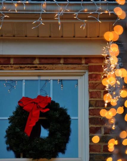 Рождественский венок висит на окне, как огни начинают мерцать, как сумерки множеств в процессе установки.  (Gene Суини Jr. / Baltimore Sun)