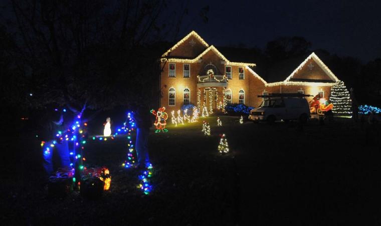 "Рон Alyman, от Фредерика, штат Мэриленд, компания ""Король Рождество"", ставит штрихи на дерево перед домом Timonium.  (Gene Суини Jr. / Baltimore Sun)"