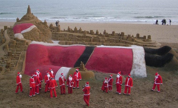 Artists dressed in Santa Claus costumes stand after creating a sand sculpture of Santa Claus as part of Christmas celebrations on a beach in Puri, located in the eastern Indian state of Orissa, December 24, 2011. (Stringer/Reuters)