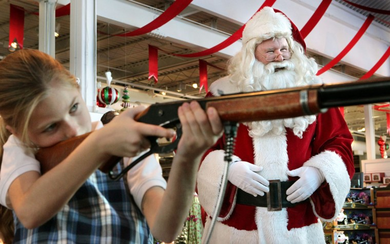 Santa Claus (right), also known as Jim Keithly, watches as Leah Freeman, 8, of St. Charles, takes aim with a laser air rifle game in Santa's Wonderland at Bass Pro Shops in St. Charles, Missouri on November 13, 2012. (Robert Cohen/St. Louis Post-Dispatch/MCT)