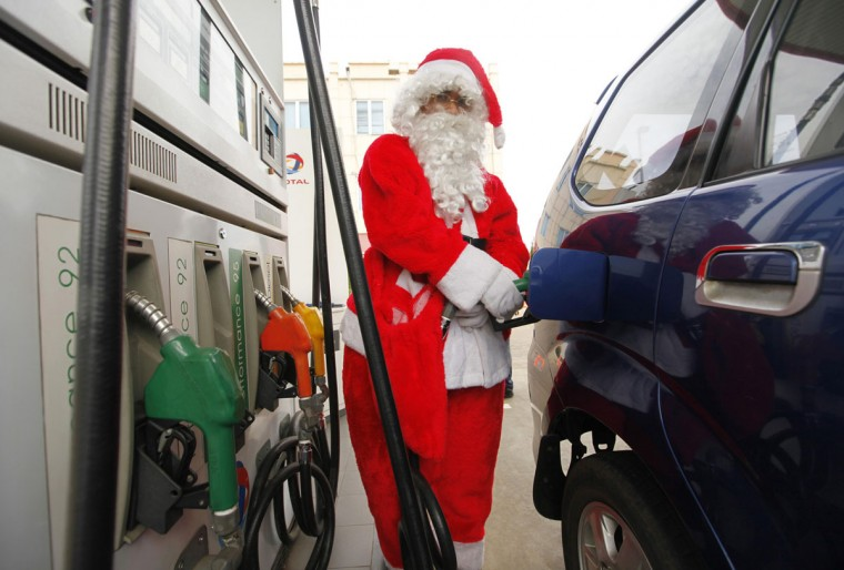 A worker dressed as Santa Claus pumps fuel into a car at a gasoline station in Indonesia city of Tangerang, ahead of Christmas December 23, 2010. (Beawiharta/Reuters)