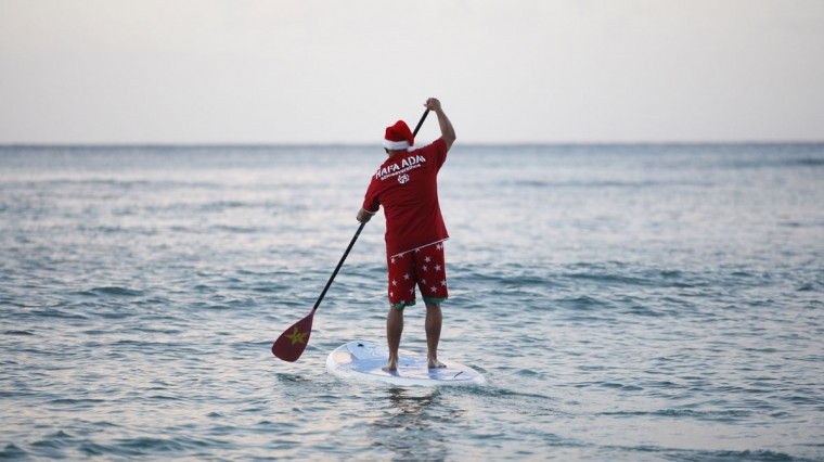 Waikiki Beach surfing instructor John Kepoo wears a Santa hat as he paddles out to the waves at sunrise on Christmas morning in Honolulu, December 25, 2011. (Jason Reed/Reuters)