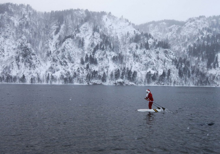 Nikolai Vasilyev water-skis while dressed as Santa Claus along the Yenisei River outside Russia's Siberian city of Krasnoyarsk December 22, 2011. Vasilyev, 58, a teacher of the Krasnoyarsk Aerospace College, constructed the self-made water skis to travel on the water surface. The skis are made of plastic foam and the sticks are designed to propel him forward. (Ilya Naymushin/Reuters)