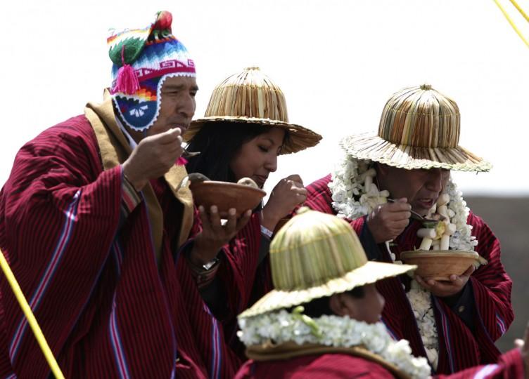 Президент Боливии Эво Моралес (слева) и иностранные ministerr Давид Чокеуанка съесть миску ухи на корабль Tunupa в озере Титикака на 16 декабря 2012 года.  На следующий день был первым из шести дней празднования в честь окончания календаря майя 21 декабря, которую некоторые считают, что конец света, но коренные боливийцы рассматривать как изменение времен.  (Gaston Брито / Reuters)