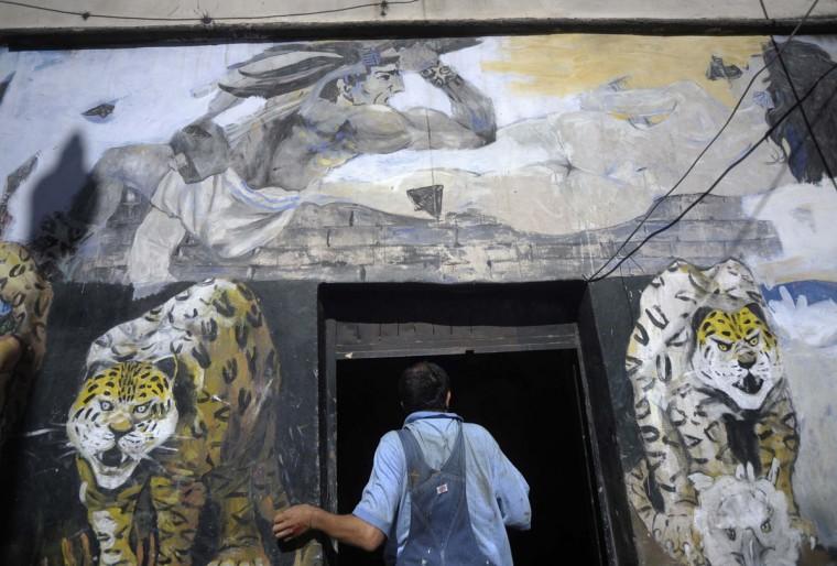 """Гондурасский художника городских Нельсон Сальгадо стоит у входа в свою мастерскую в Тегусигальпа рядом с фреской под названием """"Завоевание"""", которая изображает майя символов.  Сальгадо планирует рисовать по меньшей мере 15 картин, связанных с текущим календарем майя Длинный граф, который заканчивается 21 декабря 2012 года.  В то время как некоторые думают, что конец календаря является предсказание апокалипсиса, исследователи говорят, что дата знаменует собой начало нового календарного цикла.  (Хорхе Кабрера / Reuters)"""