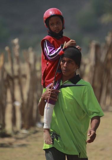 Ребенка жокей Герман Sarifudin проводится отца Германа, как ходит в начальную ворота перед гонкой на трассе за пределами Бима.  Фото сделано 18 ноября 2012.  (Beawiharta / Reuters)