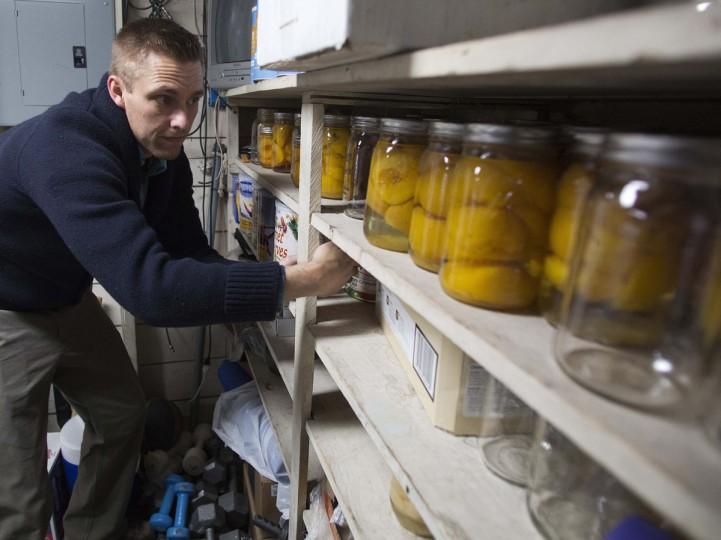 """Хью Vail запасы его хранения продуктов в своем доме в Bountiful, Юта, на 10 декабря 2012 года.  Vail является частью """"prepper"""" движение, группа людей, активно готовится к чрезвычайным ситуациям.  Хотя большинство preppers скидка пророчество майя конец света календарь, многие по-прежнему готовится к потенциальной катастрофы в конце года подходах.  (Jim Urquhart / Reuters)"""