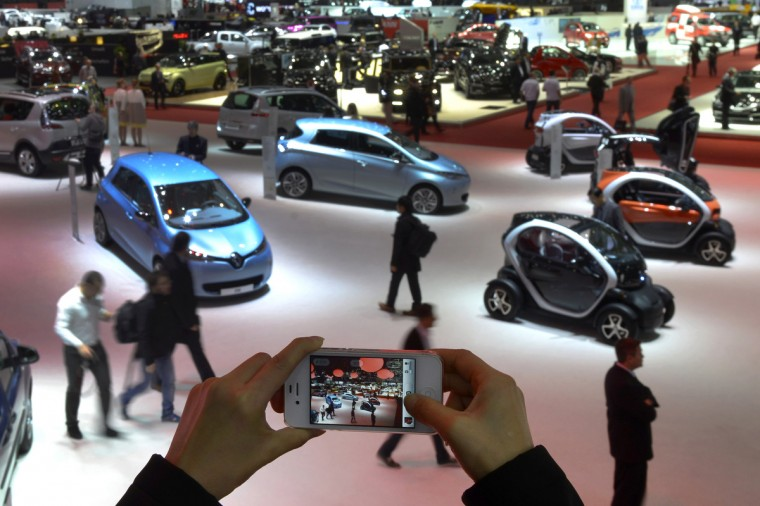 A person takes a picture of cars on March 5, 2013 on the press day of the Geneva car Show in Geneva. (Sebastein Feval/Getty Images)