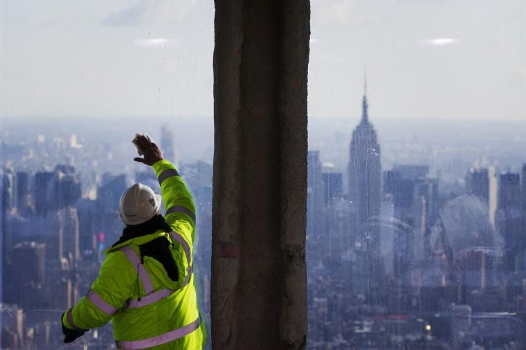 В Эмпайр Стейт Билдинг, Здание видно издалека, как Рабочий чистит windows. (Reuters/Лукас Джексон)