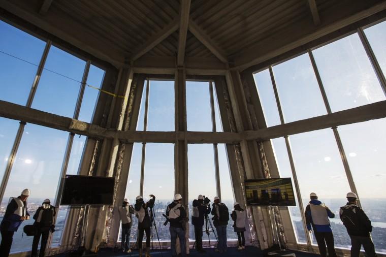 Представителей средств массовой информации принять фотографии Нью-Йорка через окна 100-й пол смотровой площадки. (Reuters/Лукас Джексон)