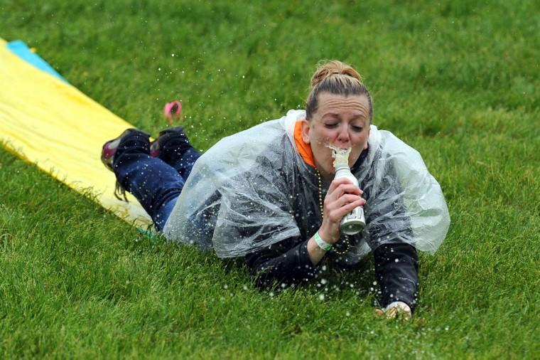 Гонки вентилятор скользит вниз скольжения N Slide в приусадебного участка, в то время как идет дождь, до 139-й работает Дерби Кентукки на ипподроме Черчилль в Луисвилле, штат Кентукки.  (Джейми Цена / Getty Images)