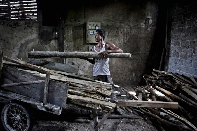 Работник имеет дрова Ми летек Srandakan завод в деревне, Bantul 22 мая 2013 года в Джокьякарта, Индонезия. Ясир Feri Ismatrada взял на себя семейный бизнес производства Ми летек основанной его покойный дед. Одну тонну каменного цилиндр поворачивается на коров, чтобы молоть муку, технику редко можно увидеть сегодня. Ясир ставит большое значение на справедливое отношение к своим 40 сотрудникам управления прибыли ограничен на уровне 10%, приоритетности интересов персонала. Ми летек продаются за 8000 рупий или $ 80 центов за килограмм. (Ulet Ifansasti / Getty Images)