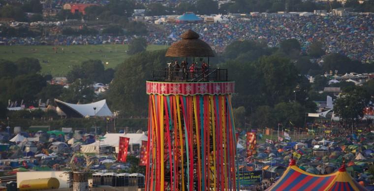 Гости фестиваля смотреть со смотровой башни на первый день фестиваля Гластонбери современного исполнительского искусства Glastonbury рядом, юго-западе Англии 26 июня 2013 года.  (Andrew Cowie / Getty Images)