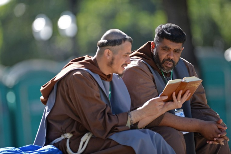 Franciscan friars read at the San Joaquin Episcopal Palace in Rio de Janeiro, Brazil, before the arrival of Pope Francis, on July 26, 2013. (Yasuyoshi Chiba/AFP/Getty Images)