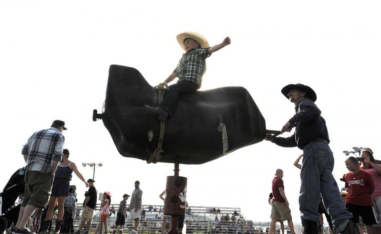 Майкл Wynkoop, 5, оф Smithsburg, штат Мэриленд едет на механическом быке с помощью профессиональных быка всадник Роберт Картер, правы.  (Lloyd Fox / Baltimore Sun)