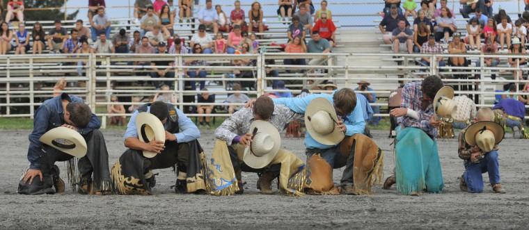 Как это принято, быка верхом ковбоев помолиться вместе во время церемонии открытия.  (Lloyd Fox / Baltimore Sun)